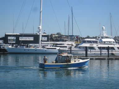 Lobsterman in Newport Harbor with mega yachts behind, Newport, RI